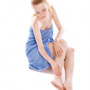 Woman in her 20s wrapped in blue towel inspecting her legs for spider veins and varicose veins