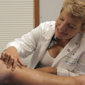 Varicose vein doctor Anne Bartel looking at a leg prior to vein surgery