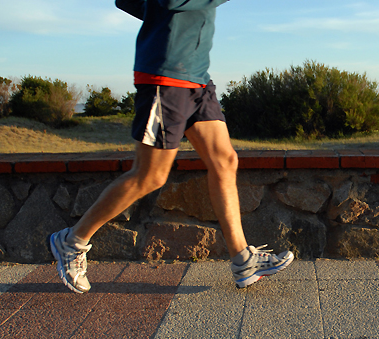 Legs of a man in blue shorts running at dawn